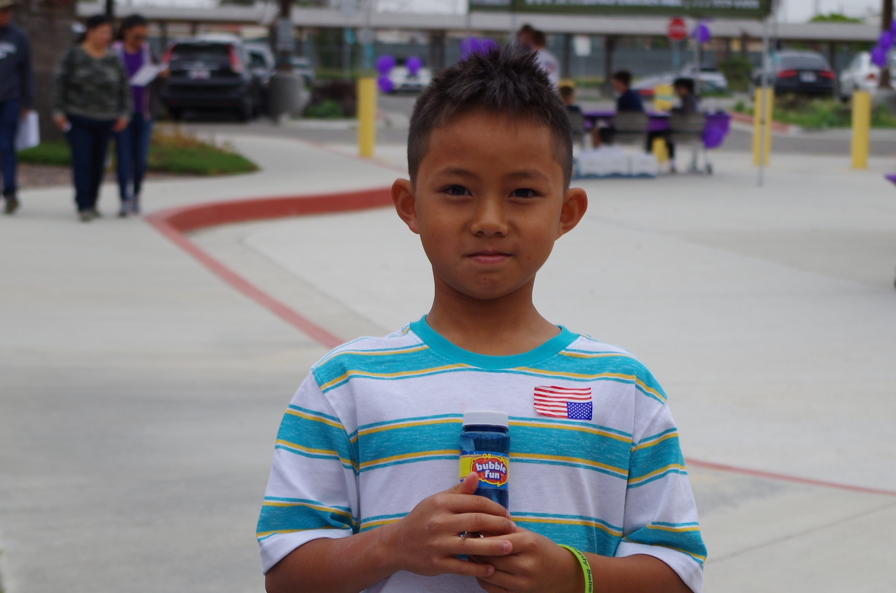 A child posing with a bottle labeled bottle fun