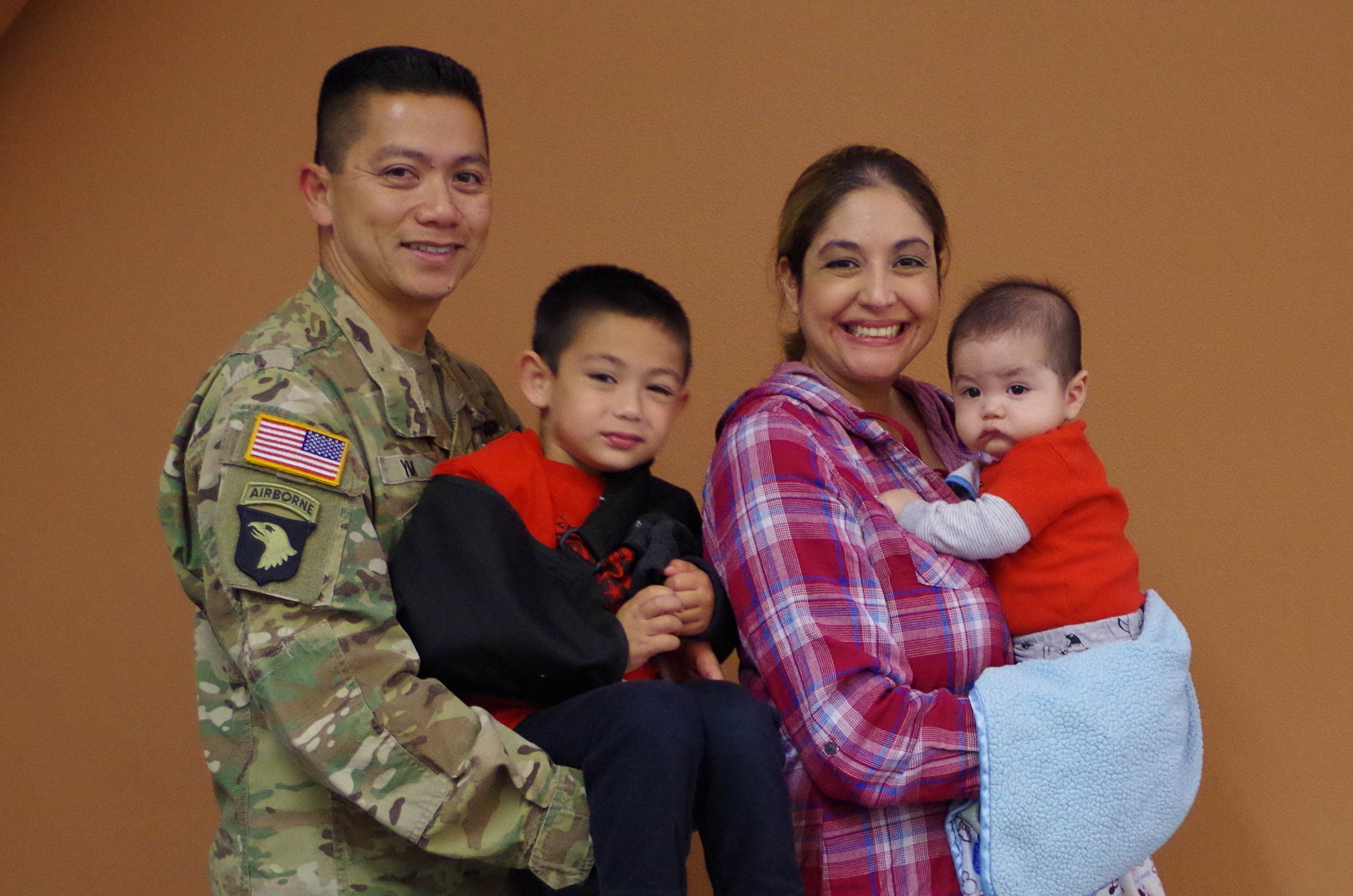 A man in US Army uniform holding a boy and a woman holding a baby