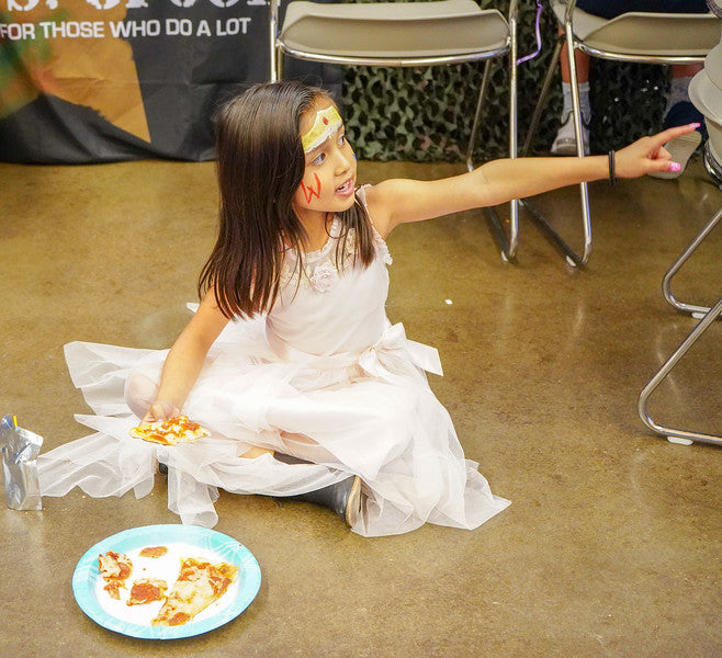 Girl sitting on the floor with Pizza, pointing to the right
