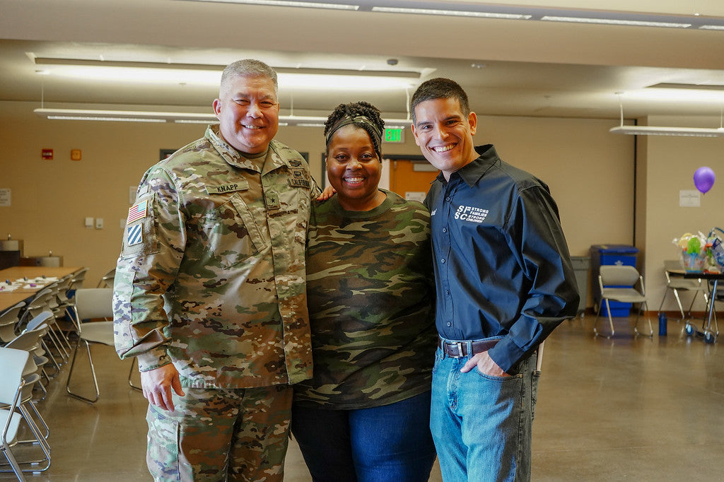 Two people posing with a man in US Army uniform