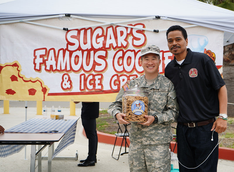A man and a man in US Army uniform posing in front of a banner titled, Sugar's famous cookies and ice cream