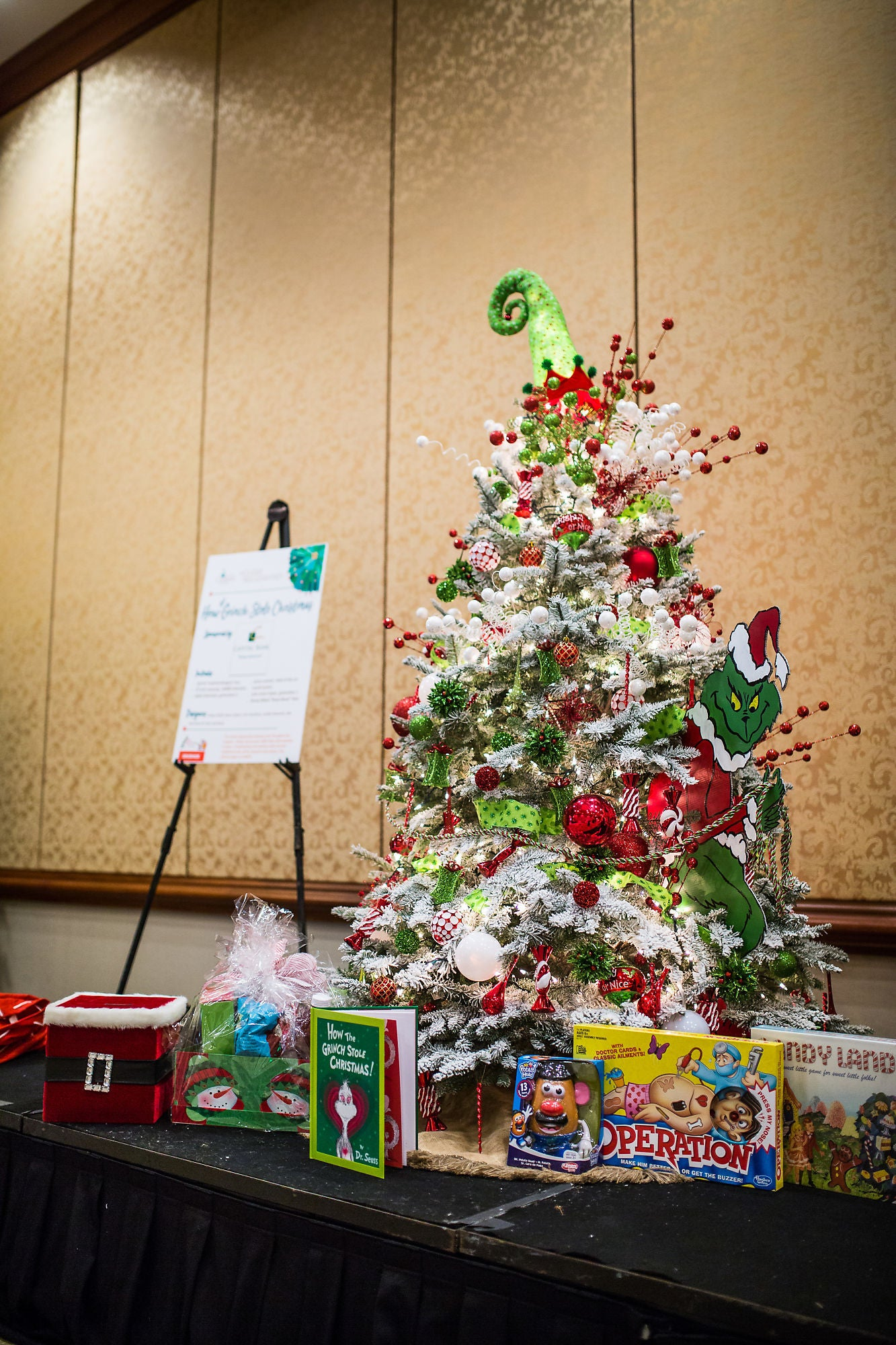 A grinch themed Christmas tree surrounded by toys and an information board
