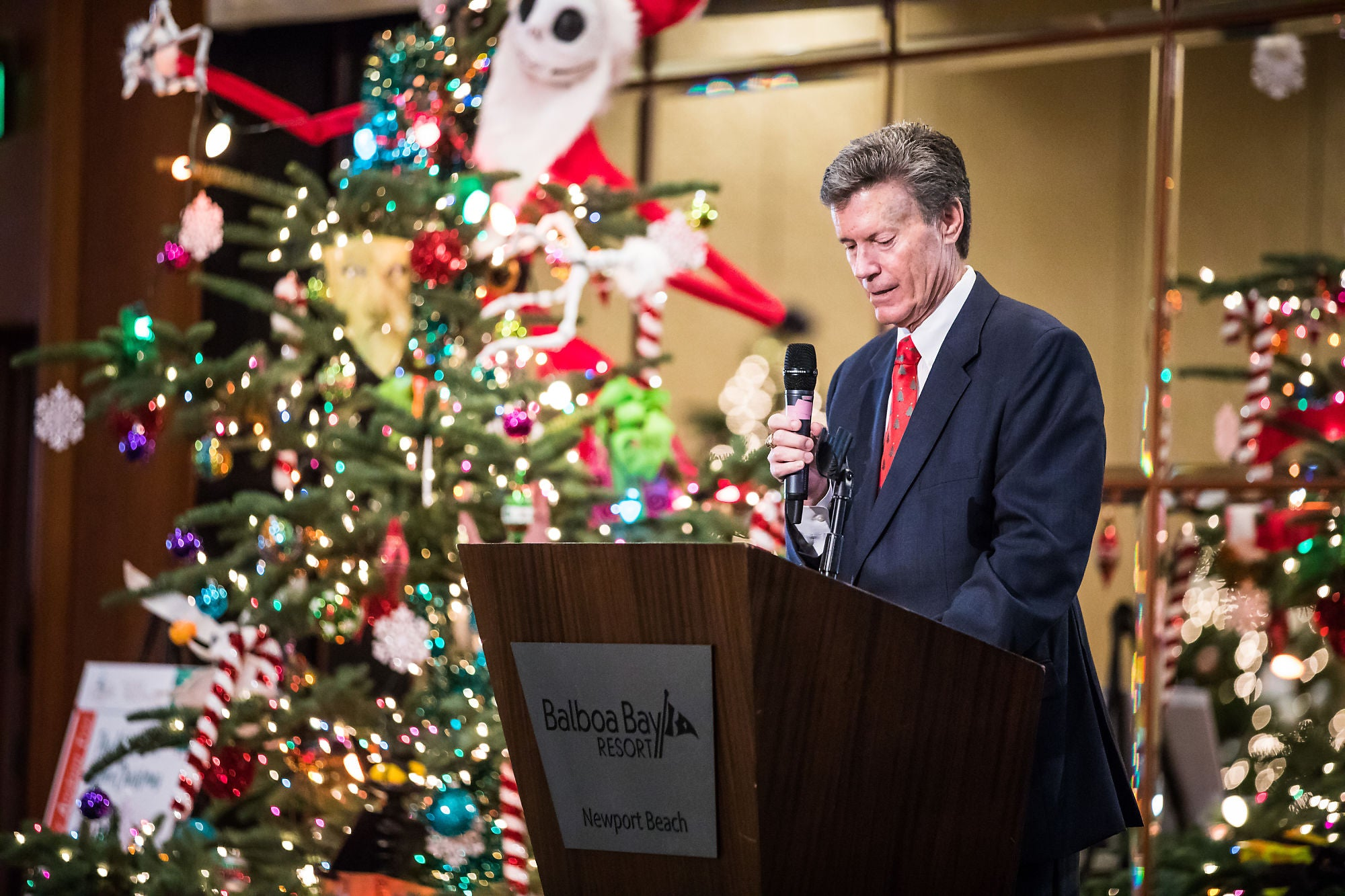 Person giving speech behind a podium, surrounded by Christmas decorations