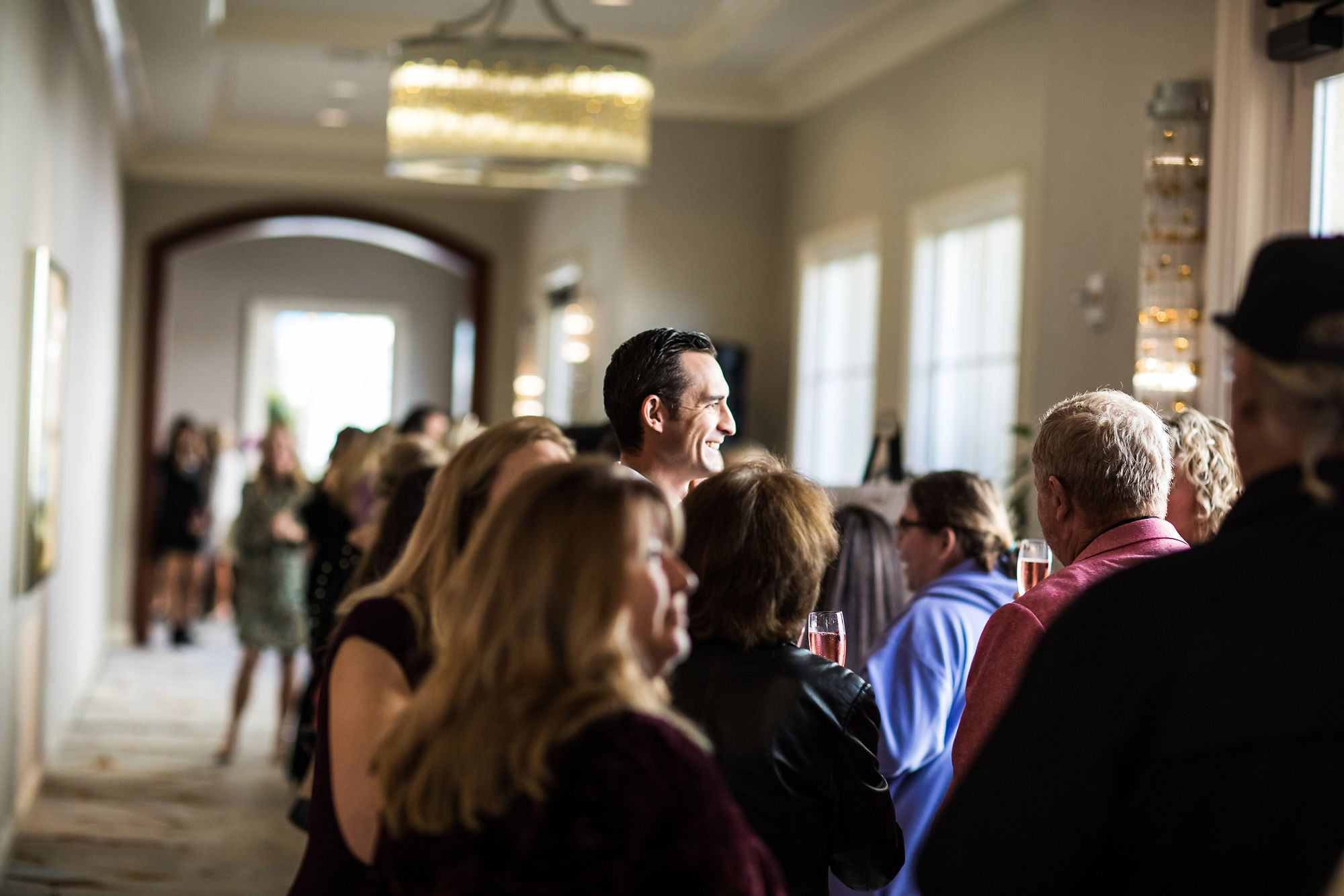 A man in focus among the crowd in a hallway