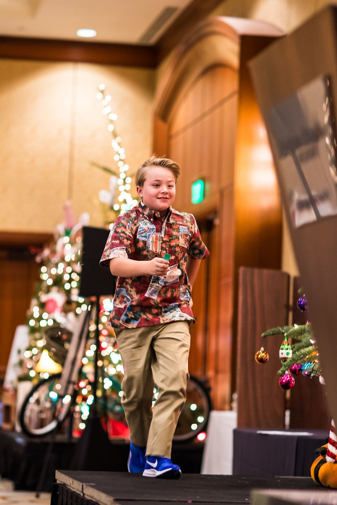A child running on stage with Christmas decorations in the background