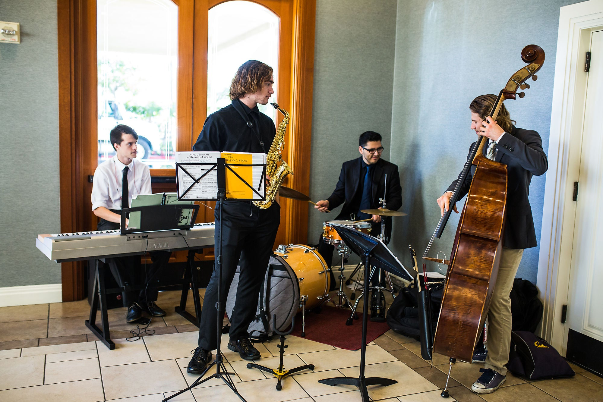 Four people playing piano, saxophone, drums, and double bass respectively