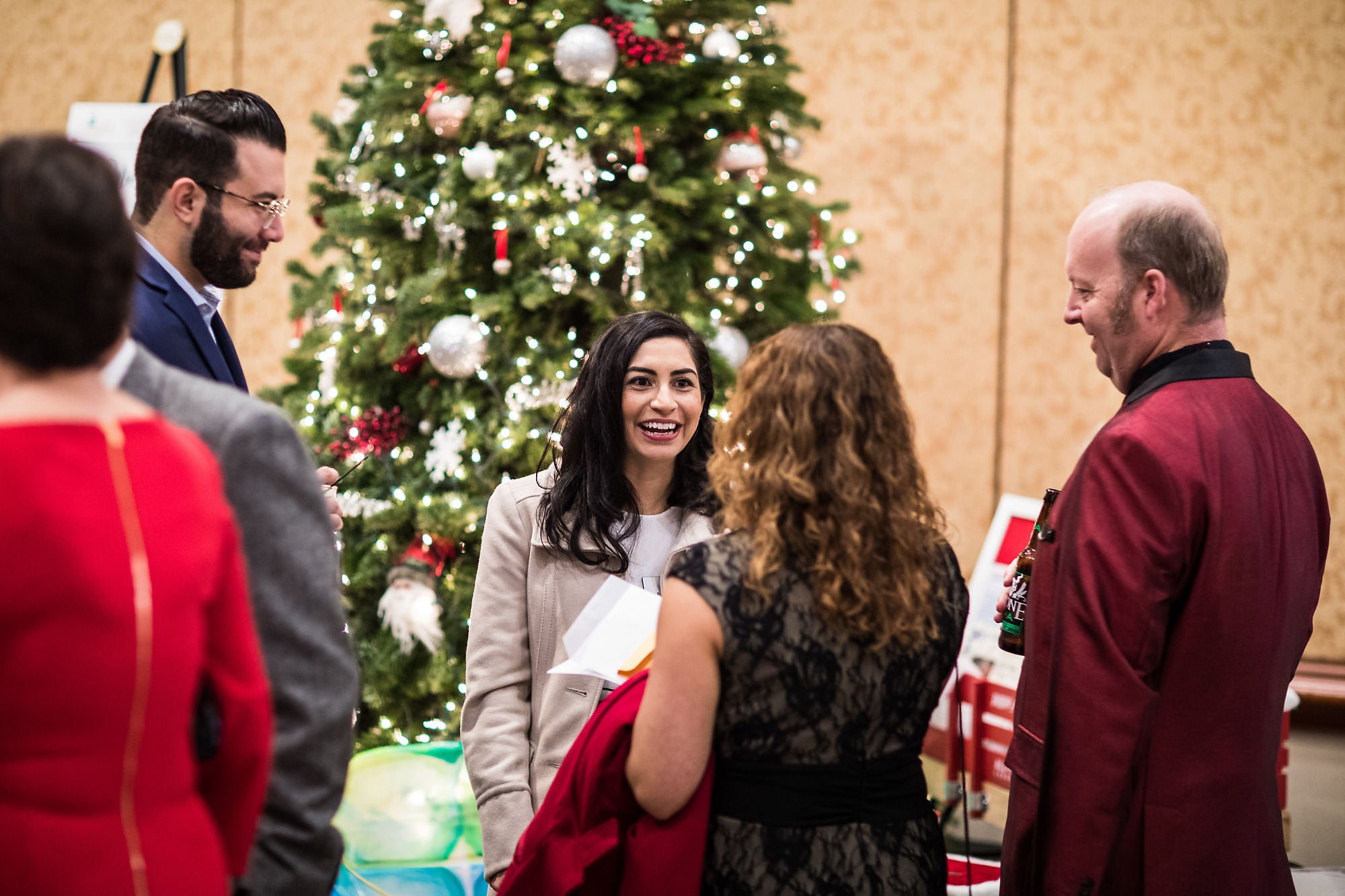 Four people conversing in front of a Christmas tree