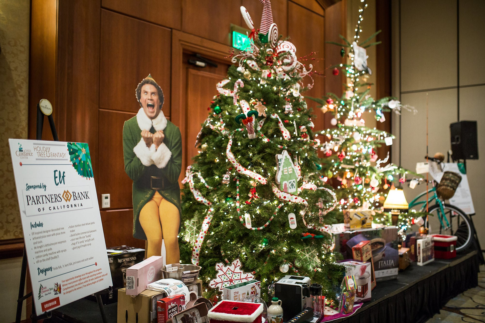 An Elf themed booth decorated with an Elf (Will Ferrell) cardboard standout, Christmas tress surrounded by items, and an information board