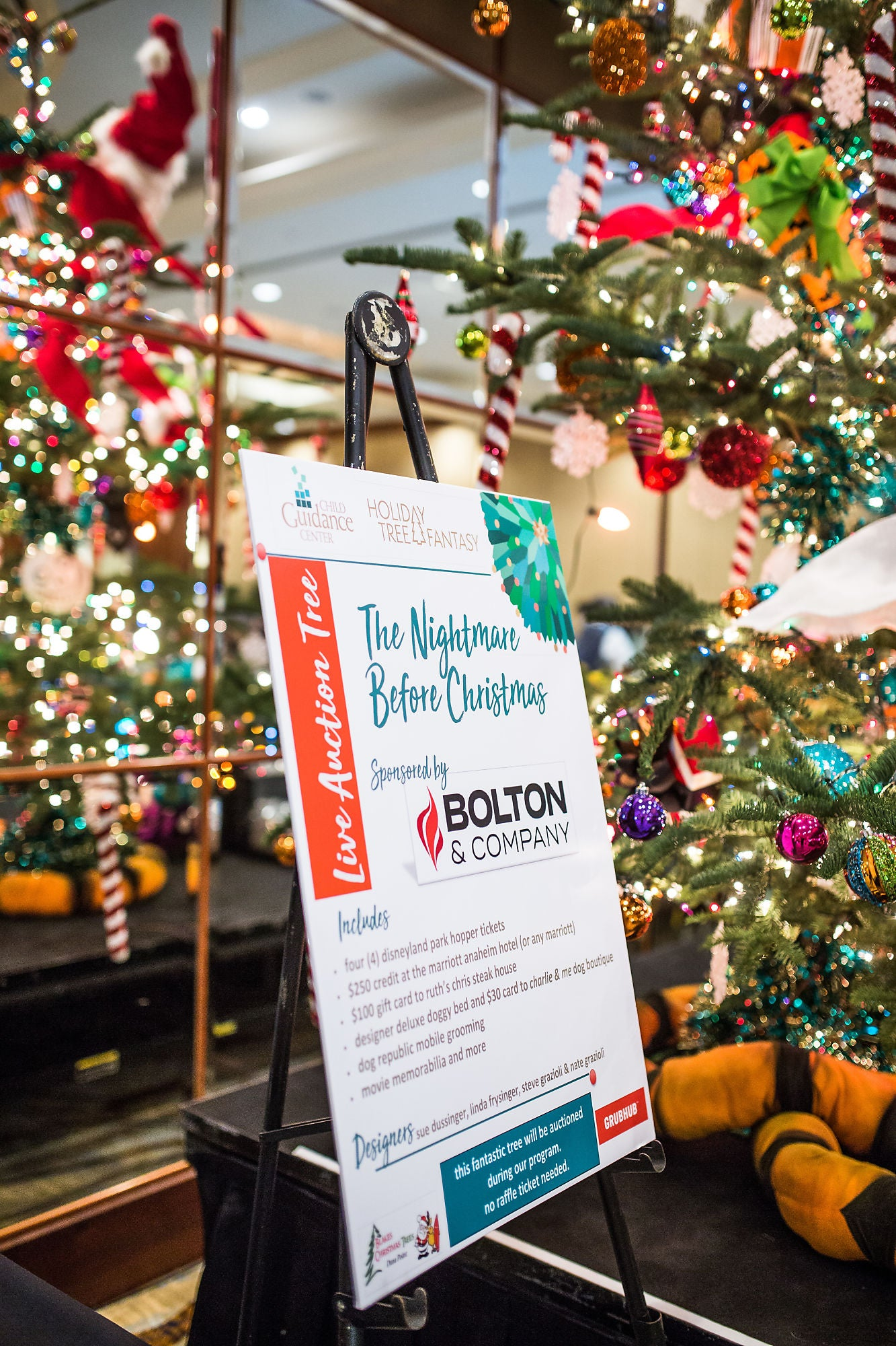 An information board explaining an auction item, placed next to Christmas trees