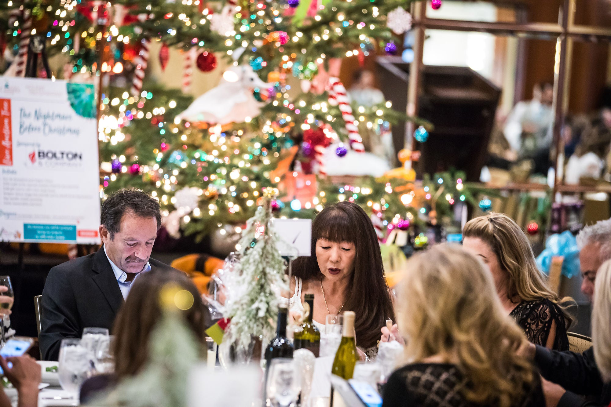 People sitting at a table, surrounded by Christmas decorations