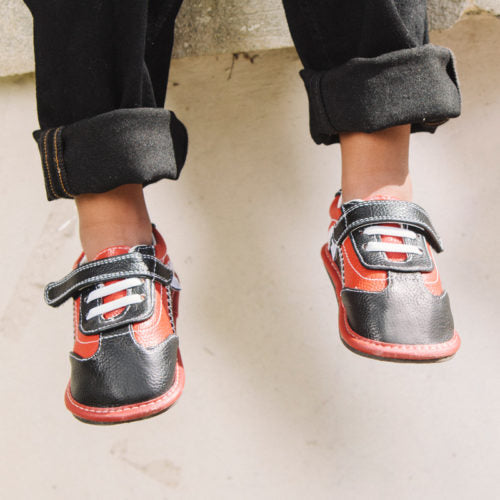 A up close photo of a toddler wearing black and orange barefoot shoes from Jack and Lily Finn