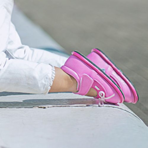A close up of a toddler wearing pink Stella children's barefoot shoes by Jack & Lily