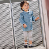 A toddler standing by a fence wearing a pair of black Lucy children's barefoot shoes by Jack & Lily