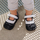 A close-up view of a pair of black Lucy children's barefoot shoe by Jack & Lily