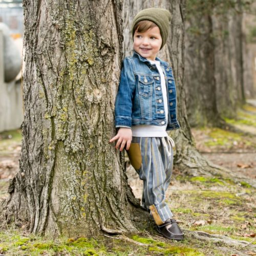 A toddler standing by a tree wearing a brown pair of Lincoln barefoot children's shoes by Jack & Lily