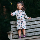 A toddler giving a thumbs up standing on a bench wearing a pair of purple Barbie barefoot shoes made by Jack and Lily