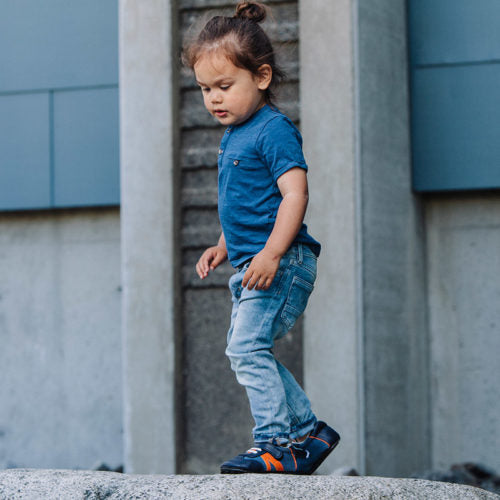 A toddler wearing a pair of blue Denny's children's barefoot shoes by Jack & Lily