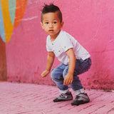 A toddler getting ready to jump in a pair of gray Emerson  children's barefoot shoe by Jack & Lily