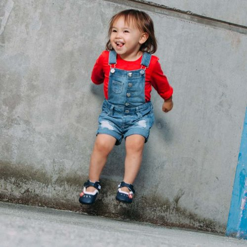 A toddler jumping while wearing a blue pair of Charlotte children's barefoot shoes by Jack & Lily