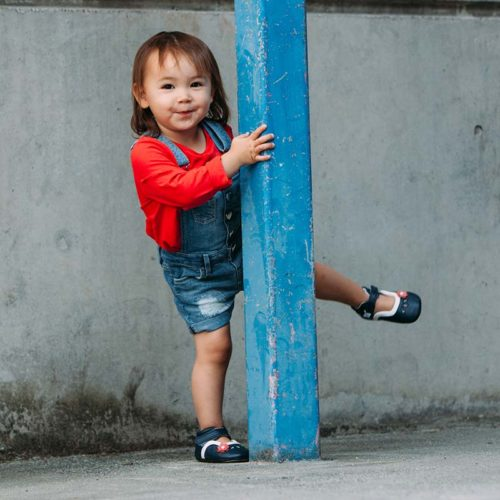 A toddler having fun wearing a blue pair of Charlotte children's barefoot shoes by Jack & Lily