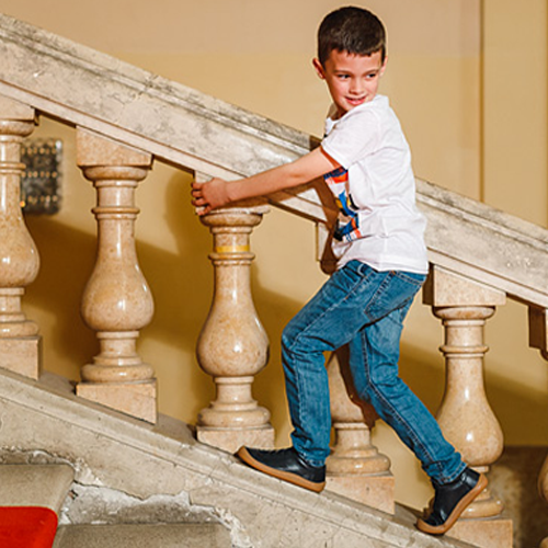 Photo of boy walking up stairs in Froddo's Barefoot gym shoes. healthy minimalist shoes for kids