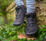A close up view of a big kid wearing black Junior Bootees by Freet minimalist shoes