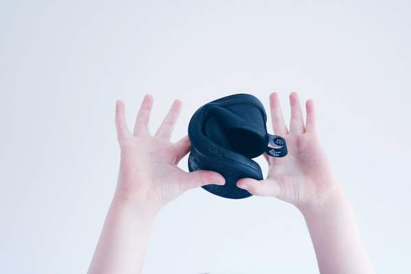 A toddler holding up a single Atlas shoes by PaperKrane kids minimalist flexible sole