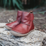 Froddo Red Winter Toddler Minimalist Boots Wool Lined barefoot boots sitting on rock in nature