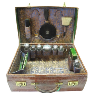 An exquisite antique (1901-1911) crocodile skin vanity case with sterling silver accessories.