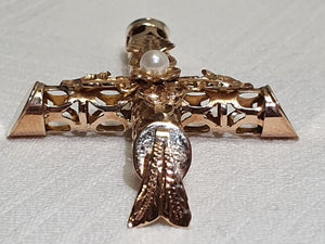 An ornate 14ct gold cross with a pearl centre piece