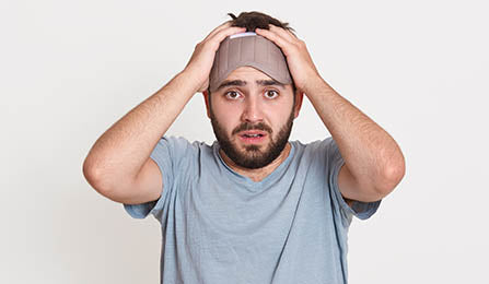 man with a sleep mask looking confused