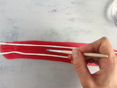 Brushing red fondant with water to stick on cake decorations