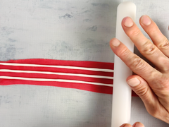 Fondant rolling pin flattening white stripes for cake decorating
