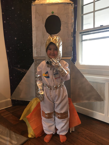 Little boy in space astronaut costume for rocket birthday party