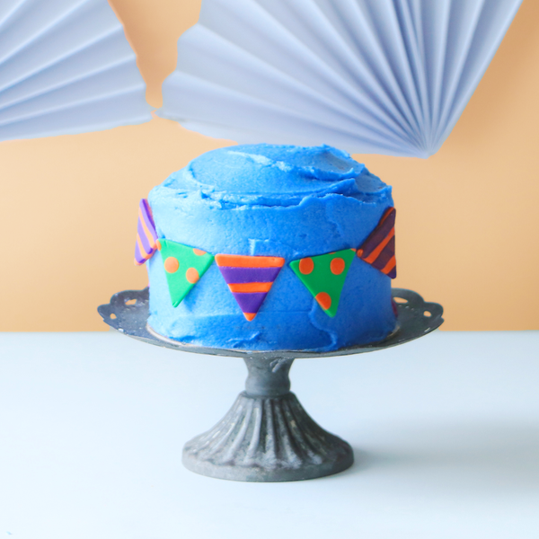 Polka dot and striped bunting on a blue mini cake.