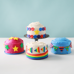 Four mini cakes, decorated with colored buttercream and fondant
