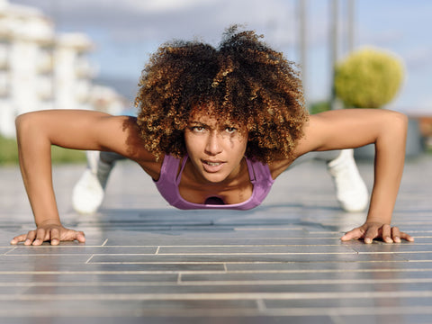 Fit woman doing push ups working out on the streets doing pushups on the floor and looking at the camera.