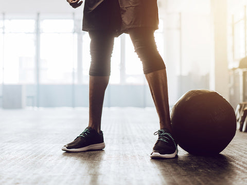 Athletic man standing in the gym beside a medicine ball. Close up of the lower half of a man working out in the gym.