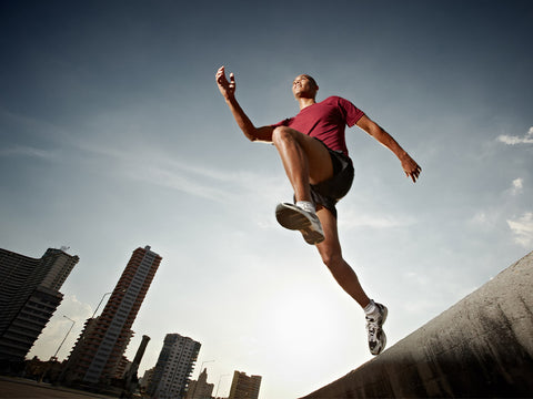 Latin american athlete running in Havana, Cuba and jumping from a high concrete step.