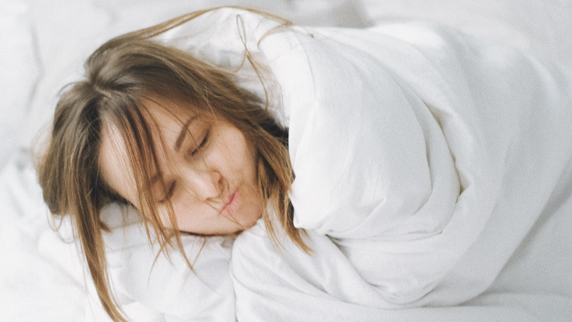 Woman covered in sheets getting beauty sleep