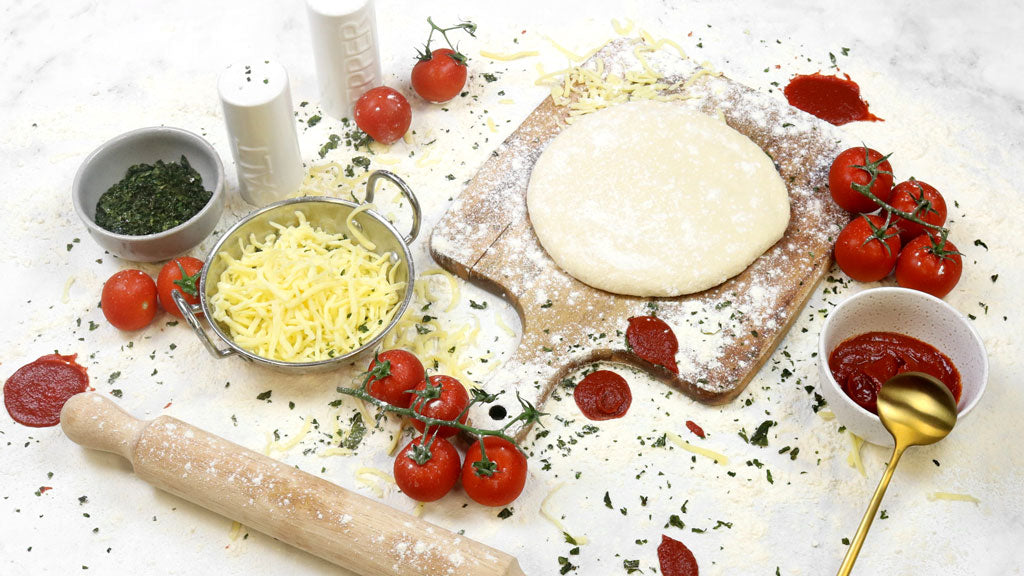 Messy pizza ingredients on table