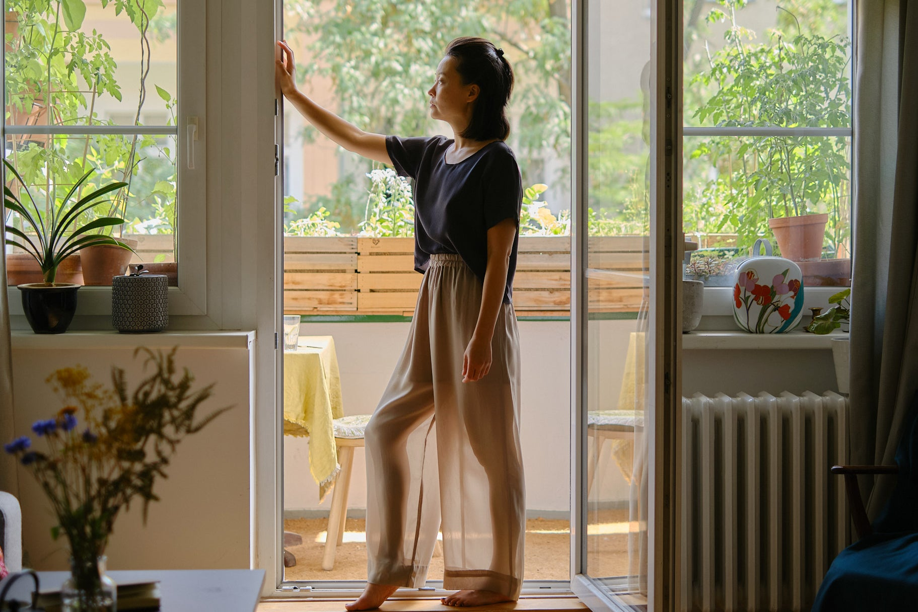 Sun Mee Martin standing in front of the balcony in her Berlin apartment