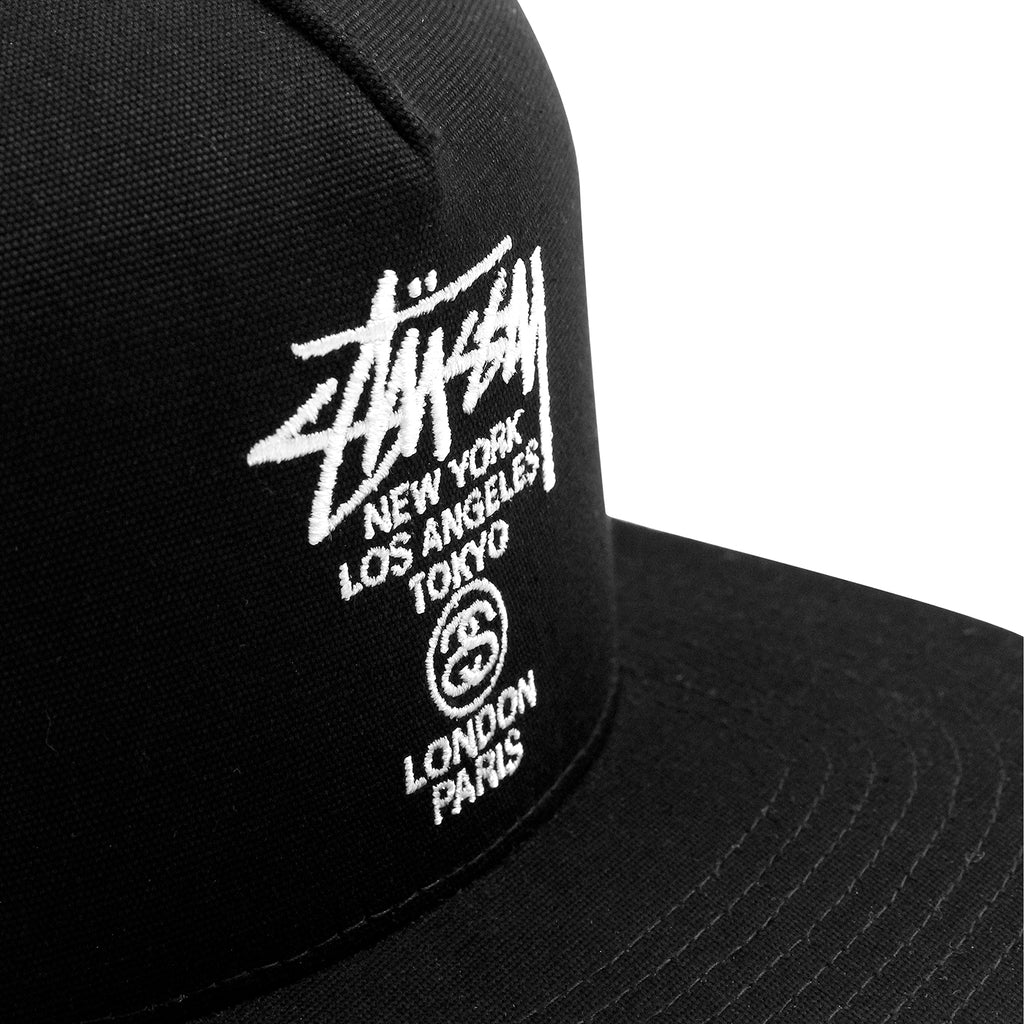 86bb7f32e60 Stussy World Tour Canvas Snapback Cap in Black - Front embroidery
