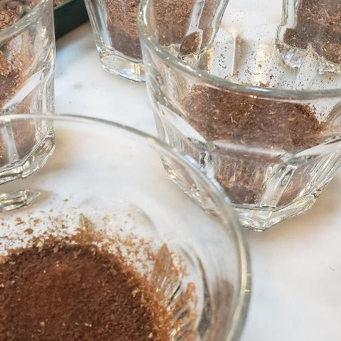 ground coffee in glass cups on a white tabletop.