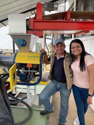 coffee farmers in colombia with the pulping machine that produces washed coffee beans