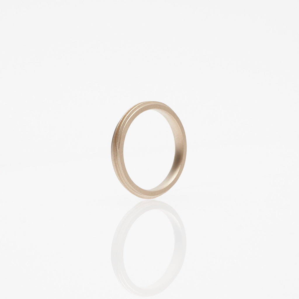Gleichenia COIL ring in 18 karat raw white gold has a spiral line spanning outer edge.