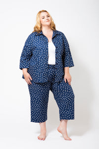 Blue Pyjamas with White Spots on a Plus Size Model wearing a White Singlet underneath the open top.