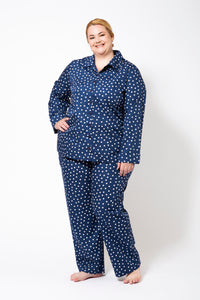 Blue Pyjamas with White Spots on a Plus Size Model. Pyjamas have Long sleeves and long pants.
