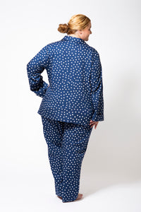 Back View of Blue Pyjamas with White Spots on a Plus Size Model.  Pyjamas have long sleeves and long pants.