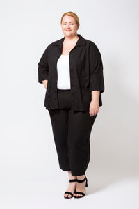 Plus Size Model in Black Cotton Pants and Black Cotton Button-Up Shirt left open with a white singlet underneath.